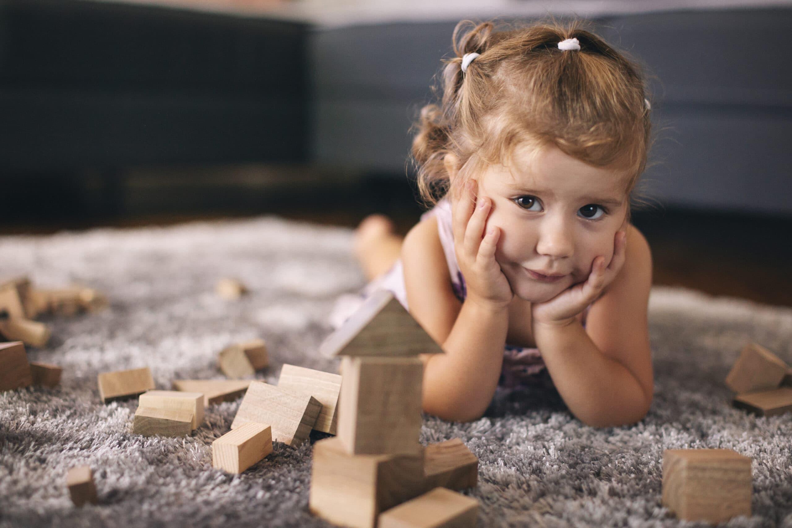 Bambina che gioca sul tappeto con le costruzioni